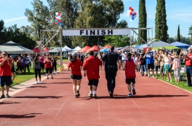 Special Olympics Southern California LA/SGV Pomona Area Games April 22, 2017 flame presentation with Azusa police chief Stephan Hunt and his daughter volunteer Madison Hunt with crowd cheering at finish line